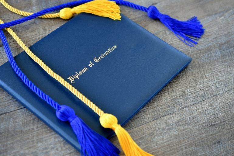 Flat lay of a diploma of graduation with honor cords on a simple wooden background achievement t20 o R19a W